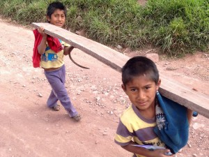 peruvian boys carrying lumber near maras