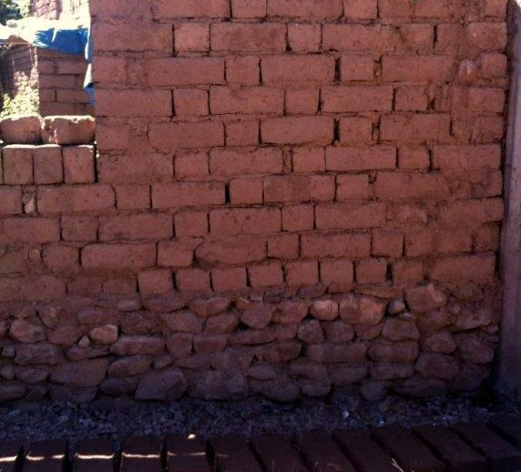 Adobe wall with a protected base