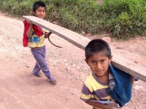 peruvian boys carrying lumber near maras