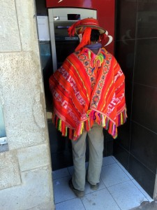 Quechua speaker in traditional garb using ATM